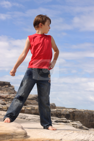 Child outdoors in the summer sun stock photo, Child outdoors in the summer sun standing on rocks with a pretty blue sky and clouds behind him. by Leah-Anne Thompson