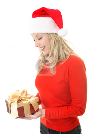 Smiling woman holding a Christmas gift stock photo, A smiling woman receiving a Christmas gift.   She is looking down and smiling in appreciation. by Leah-Anne Thompson
