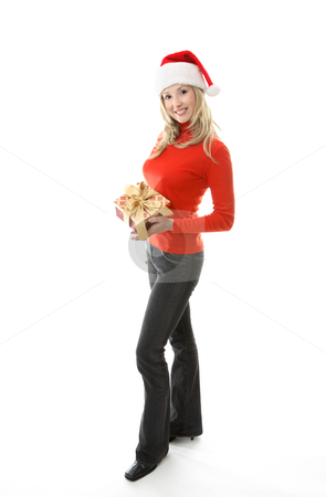 Happy Woman holding Christmas Present stock photo, Friendly girl in black pinstripe jeans and red  polo neck sweater standing on a white background.  She  is holding a Christmas present wrapped with a gold ribbon and smiling. by Leah-Anne Thompson