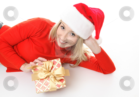 Girl with Christmas Present stock photo, Smiling girl lying on the floor casually and holding a Christmas present. by Leah-Anne Thompson