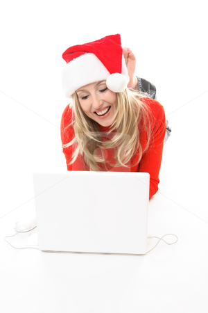 Christmas girl shopping browsing internet stock photo, Christmas girl using a laptop to shop or browse the web online. She might also be studying chatting to friends or family  or electronic banking, etc.    She is wearing a festive santa hat and smiling. by Leah-Anne Thompson