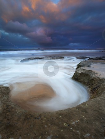 Sunrise Spin Cycle stock photo, A natural bowl catches the rising tides in a spin cycle as dawn' s first light hits the passing storm clouds over Knight's Beach by Mike Dawson
