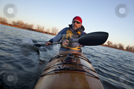 Paddling workout in a sea kayak stock photo, Mature male paddler exercising (turning boat using rudder stroke with his wing carbon fiber paddle) in a home built wooden sea kayak on lake, fall scenery  in Colorado, view from kayak bow by Marek Uliasz