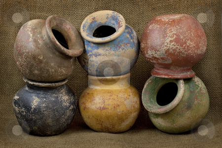 Six clay plant pots with grunge finish stock photo, Six small plant clay pots (mass produced planters) with rough color finish on dark burlap texture background, still life by Marek Uliasz