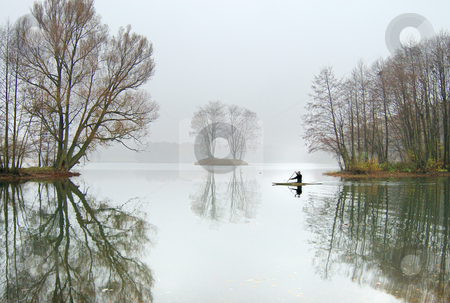 On cold water stock photo, The oarsman in a boat floats on lake in November. by Vladimir Blinov