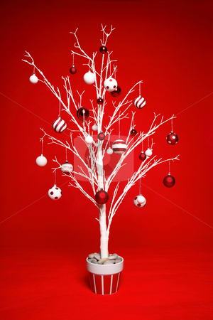 Christmas tree with red and white baubles stock photo, White modern Christmas tree decorated with various red and white themed christmas baubles (balls) on a red background. by Leah-Anne Thompson