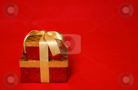 Wrapped present on a red background stock photo, A wrapped gift box tied with gold satin ribbon on a red background.  Space for copy by Leah-Anne Thompson