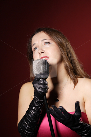 A sexy singer with a vintage microphone stock photo, A sexy singer with a vintage microphone on red background by Remy Musser