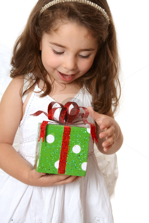 Little girl with a christmas or other present stock photo, A little girl with browin hair looks down in delight at a Christmas present by Leah-Anne Thompson