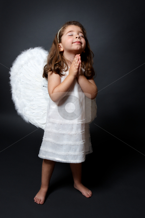 Praying angel with hands together in worship stock photo, Little barefoot angel in white dress and feathered wings with hands together in quiet prayer by Leah-Anne Thompson