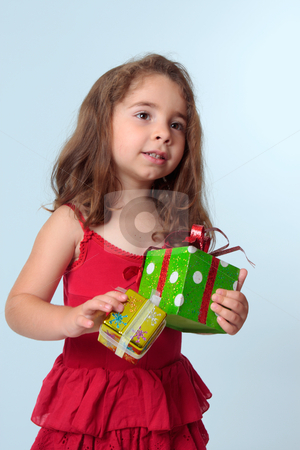 Little girl holding Christmas presents stock photo, Young preschool girl holding presents.  She is wearing a red dress. by Leah-Anne Thompson