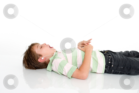 Child listing to music stock photo, Child lying down listening to mp3 music by Leah-Anne Thompson