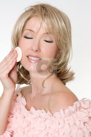 Makeup Removal stock photo, An adult woman using a cosmetic sponge to begin removing makeup. by Leah-Anne Thompson