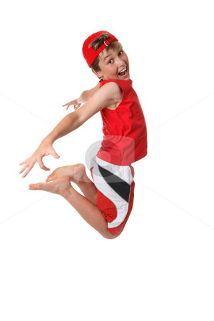 Happy boy mid jump stock photo, A happy boy full of vitality jumps off the ground with hand and legs back by Leah-Anne Thompson