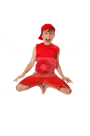 Excited boy jumping off the ground. stock photo, Thrilled boy jumps off the ground with feet in tight to his body. by Leah-Anne Thompson