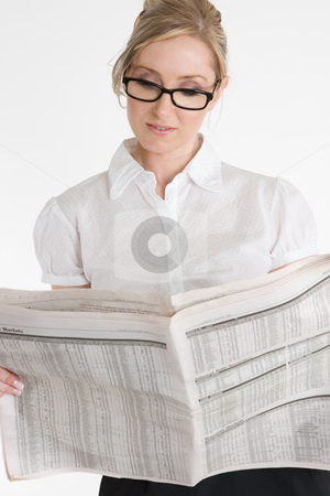 Businesswoman reading financial newspaper stock photo, A businesswoman reading the financial newspaper.  Please note newsprint has been artificially blurred to render company names illegible. by Leah-Anne Thompson