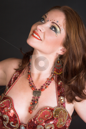 Belly Dancer in Red stock photo, Belly Dancer wearing a red costume with jewelery by Carla Booysen