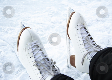 Ice skates stock photo, Ice skates. Closeup of classical figure skating ice skates on ice outdoors on lake in Quebec, Canada by Maridav
