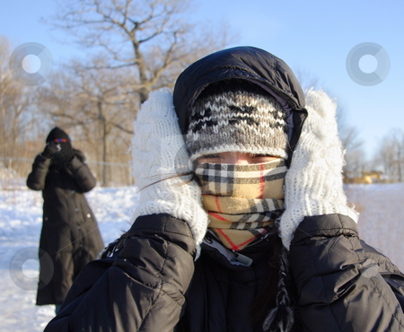 Woman freezing cold stock photo, Cold winter woman covering herself from the cold. by Maridav