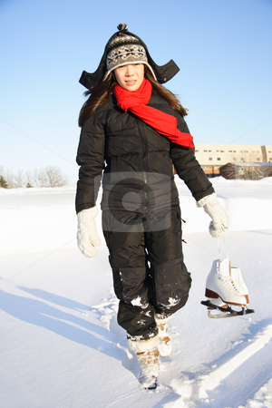 Woman going ice skating stock photo, Ice skating. Woman walking with figure skating ice skates outdoors in the snow in Quebec, Canada. by Maridav
