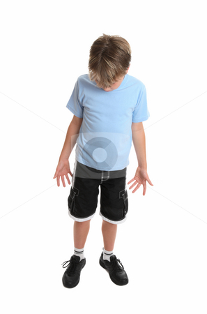 Boy looking down stock photo, Boy standing in plain blue t-shirt and shorts looking down.  Focus to head. by Leah-Anne Thompson
