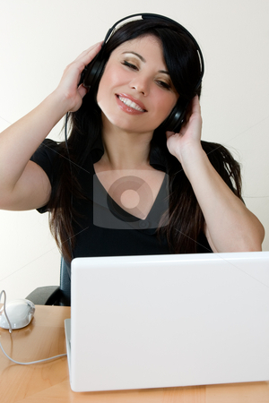 Online Music Generation stock photo, A woman listens to music through headphones. by Leah-Anne Thompson