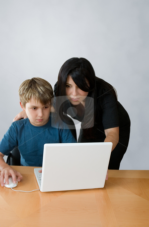 Adult assisting child on computer stock photo, An adult assists a child using a laptop computer. by Leah-Anne Thompson