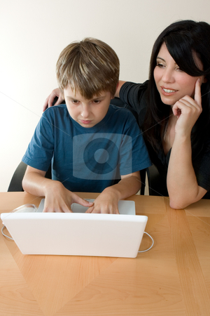 Child using laptop while adult supervises stock photo, Child using a computer with adult supervision. by Leah-Anne Thompson