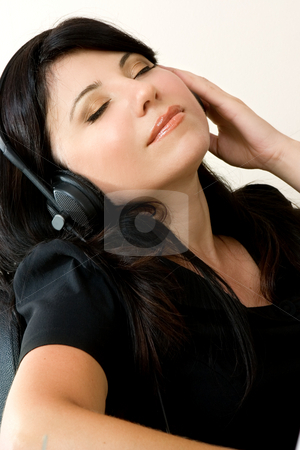 Woman listening music stock photo, A woman relaxes and listens to music through headphones. by Leah-Anne Thompson