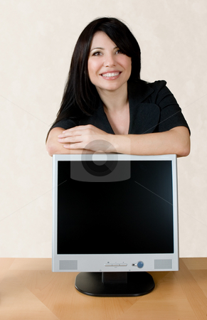 Woman leaning on lcd screen stock photo, Smiling businesswoman leans on an lcd computer screen. by Leah-Anne Thompson