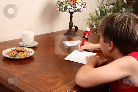 Writing a Christmas letter or card stock photo, A child sitting at a desk writing a letter by Leah-Anne Thompson