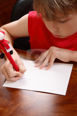 Child writing a letter stock photo, A child writing a letter to santa.  Focus to hands by Leah-Anne Thompson