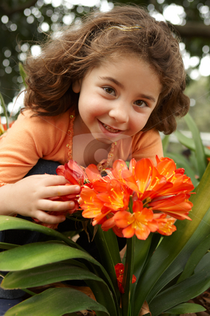 Little girl in a garden of clivia miniata stock photo, Little girl holding a bunch (umbels) of clivia miniata (bush lily) yellow orange flowers. by Leah-Anne Thompson