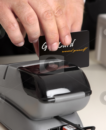 Swiping a card through a terminal stock photo, Man swiping a gift card, credit or debit card.   Original card front has been replaced including text with my own.   Focus to hand and card.  Shallow dof.  This could be a sales person or a customer.  You could also replace this with your own store card or bankcard. by Leah-Anne Thompson