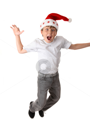 Crazy Christmas stock photo, Excited crazy boy wearing a santa hat - motion in hand and feet. by Leah-Anne Thompson