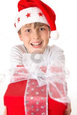 Festive child holding a present stock photo, A child holding a bright red gift tied up with silver ribbon.  Focus to boy. by Leah-Anne Thompson