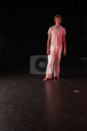 Dancer on stage stock photo, Single Caucasian male dancer standing on the stage with black background. Lit with spotlights by Sean Nel