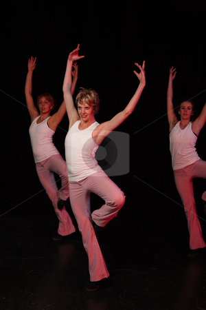 Dancers on stage stock photo, A group of three Caucasian female freestyle hip-hop dancers in a dancing training session. Lit with spotlights by Sean Nel