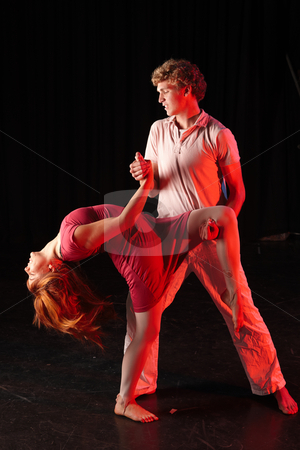 Dancers on stage stock photo, Caucasian male dancer lifting his female partner in a dancing training session on the stage with black background. Lit with spotlights by Sean Nel