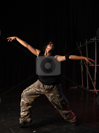 Dancers on stage stock photo, Single African male dancer dancing on the stage with black background during training session. Lit with spotlights. by Sean Nel