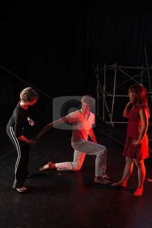 Dancers on stage stock photo, Caucasian male dancer and his female partner being instructed by their teacher and coach in a dancing training session on the stage with black background. Lit with spotlights by Sean Nel