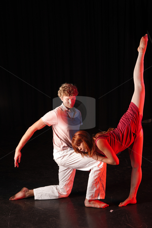 Dancers on stage stock photo, Tall Caucasian male dancer supporting his female partner in a training session on the stage with black background. Lit with spotlights by Sean Nel