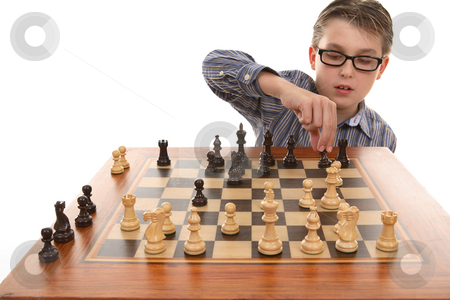 Playing a game of chess stock photo, A boy moving a chess piece on a portable chess game table. by Leah-Anne Thompson