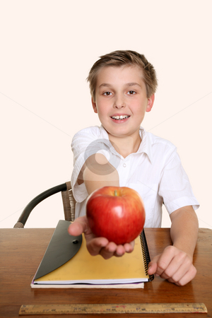 An apple for my favourite teacher stock photo, A child holds out an apple for his teacher. by Leah-Anne Thompson