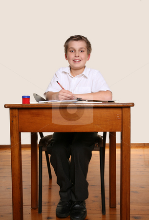 Happy school student stock photo, Happy smiling young school boy sitting at school desk/ by Leah-Anne Thompson