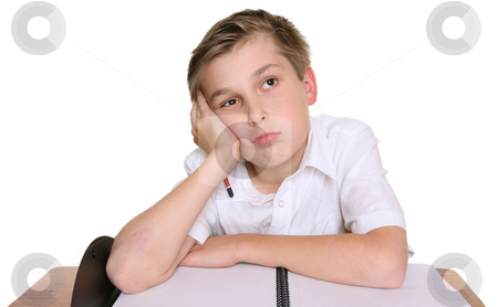 School boy lost in thought stock photo, A school student with head resting on one hand, siting in front of an empty book,  lost in thought, daydreaming, or thinking about what to write by Leah-Anne Thompson