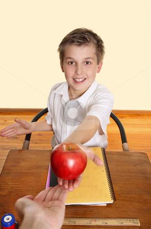 Student giving teacher an apple stock photo, A schoolboy hands his teacher a red apple. by Leah-Anne Thompson