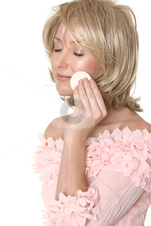 Woman using makeup applicator stock photo, A woman removing, applying or touching up makeup to her face by Leah-Anne Thompson