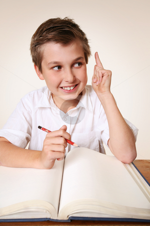 Brainchild schoolboy with idea stock photo, Student school boy sitting at desk with school books has an inspirational idea by Leah-Anne Thompson