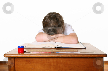 School child with head in hands stock photo, A unhappy or frustrated schoolboy sitting at desk and bent over with head in hands by Leah-Anne Thompson